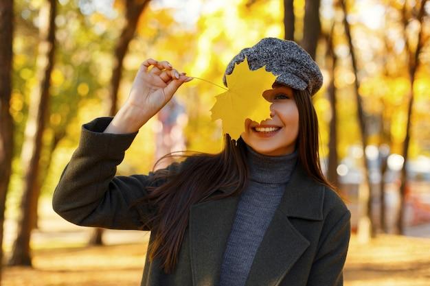 Vrolijke mooie jonge vrouw met een glimlach in modieuze vintage kleding met een jas en hoed met gele herfstblad wandelen in het park