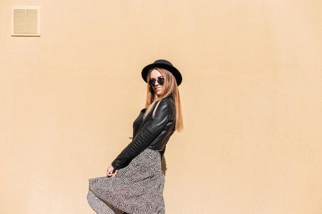 Vrolijke mooie jonge vrouw met een schattige glimlach in een mode hoed en zonnebril met leren jas in een vintage jurk genieten van het zonnige weer in de buurt van een beige muur