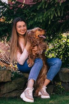 Vrolijke mooie jonge vrouw met lang haar zitten en haar hond knuffelen op de tuin in de buurt van boom.