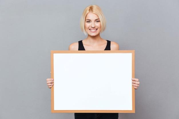 Vrolijke mooie jonge vrouw met leeg wit bord over grijze muur