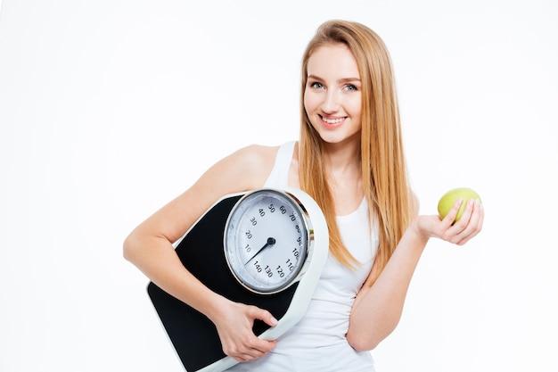 Vrolijke mooie jonge vrouw met schalen en groene appel op witte achtergrond