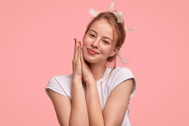 Vrolijke mooie jonge vrouw met zachte schone huid, houdt de handpalmen tegen elkaar gedrukt in de buurt van het gezicht, blij om 's ochtends een compliment te ontvangen van de echtgenoot