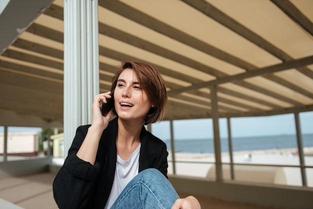 Vrolijke mooie jonge vrouw praten op een mobiele telefoon op het terras op het strand