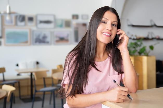 Vrolijke mooie jonge vrouw praten over mobiel, staande op co-working, leunend op bureau,
