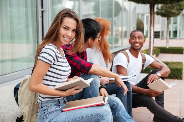Vrolijke mooie jonge vrouw zit en leest een boek met haar vrienden buitenshuis