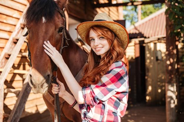 Vrolijke mooie jonge vrouwenveedrijfster met haar paard op boerderij