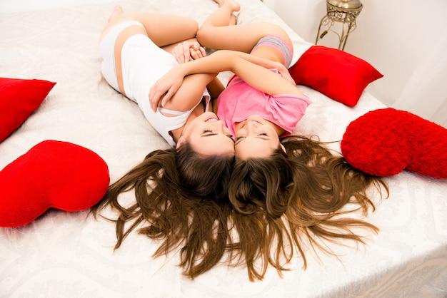 Vrolijke mooie meisjes in pyjama's die elkaar knuffelen en op het bed liggen