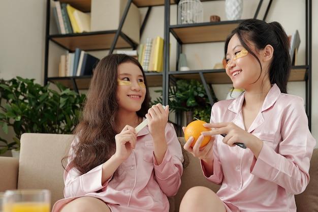 Vrolijke mooie vriendinnen in zijden pyjama's die nagels vullen en verse sinaasappels eten terwijl ze genieten van...