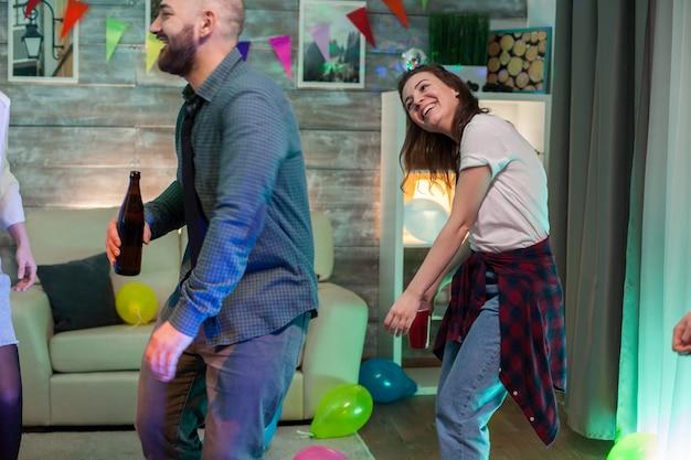 Vrolijke mooie vrouw die lacht tijdens het dansen op een feestje van een vriend.