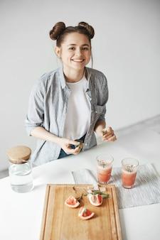 Vrolijke mooie vrouw die lacht versieren grapefruit detox smoothie met rozemarijn over witte muur. gezonde voeding.