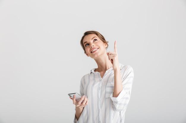 Vrolijke mooie vrouw die met de vinger naar boven wijst en een mobiele telefoon gebruikt die op een witte achtergrond wordt geïsoleerd