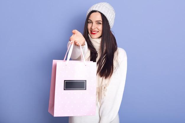 Vrolijke mooie vrouw draagt witte trui, muts en sjaal, met papieren zak