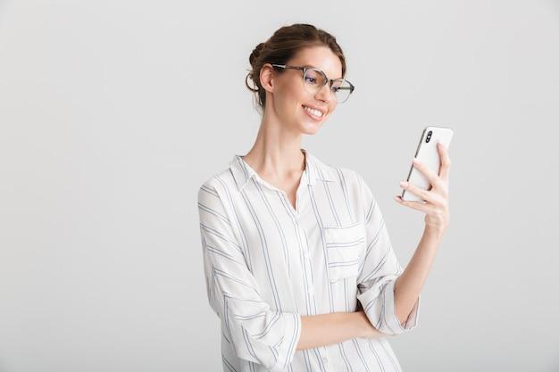 Vrolijke, mooie vrouw, in, bril, typen, op, gsm, geïsoleerde, op wit