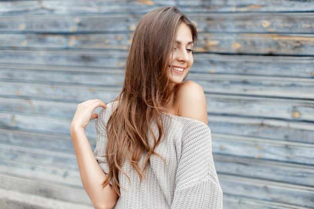 Vrolijke mooie vrouw in een grijze trui, glimlachend in de buurt van een vintage blauwe houten muur