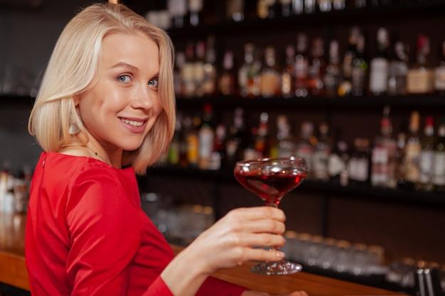 Vrolijke mooie vrouw in rode jurk vieren aan de bar, met heerlijke cocktail, kopie ruimte
