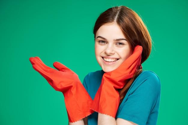 Vrolijke mooie vrouw in rubberen handschoenen emoties groene achtergrond schoonmaken
