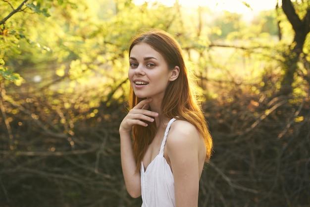 Vrolijke mooie vrouw in witte jurk natuur bomen zomer. hoge kwaliteit foto