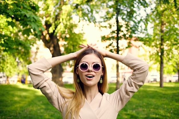 Vrolijke mooie vrouw in zonnebril buiten in het park