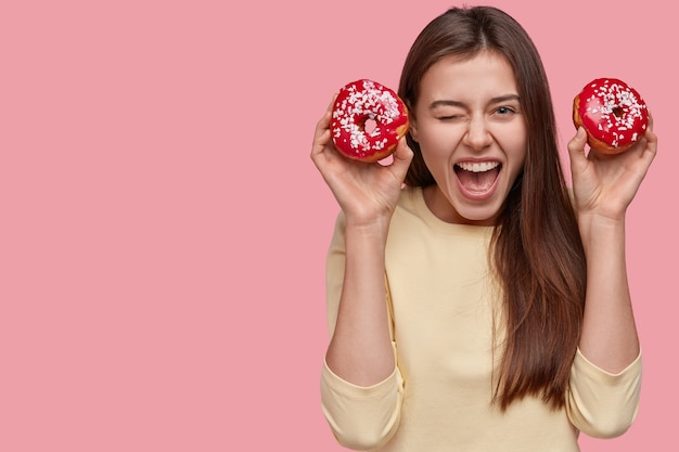Vrolijke mooie vrouw knippert met haar ogen, roept positief uit, eet heerlijke donuts, draagt een casual trui