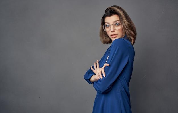Vrolijke mooie vrouw met de manier grijze achtergrond van het glazen blauwe overhemd