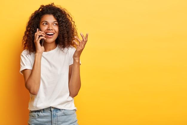 Vrolijke mooie vrouw met krullend afro haar hangt in vrije tijd aan de telefoon met de beste vriend