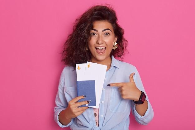 Vrolijke mooie vrouw met paspoort en vliegtickets in de hand