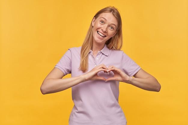 Vrolijke mooie vrouw met sproeten in lavendelt-shirt die hartvorm toont door handen en op geel glimlacht