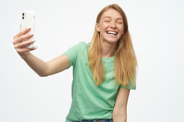 Vrolijke mooie vrouw met sproeten in mint tshirt met behulp van mobiele telefoon en lachen op wit