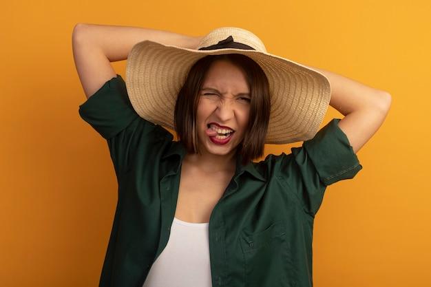 Vrolijke mooie vrouw met strandhoed steekt tong uit en legt handen op hoed die op oranje muur wordt geïsoleerd
