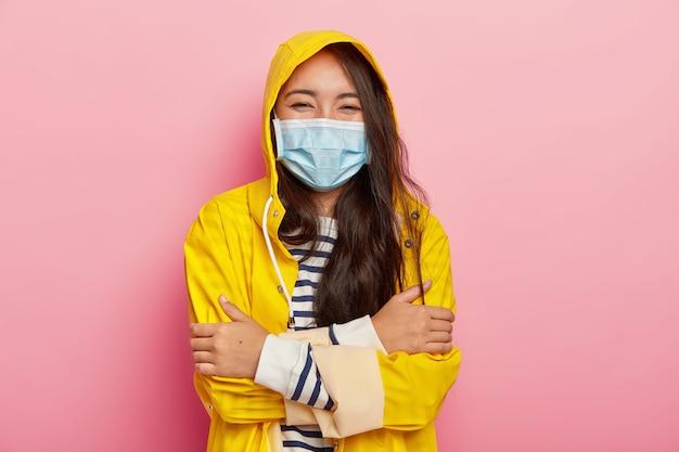 Vrolijke mooie vrouw met zwart haar, houdt armen over elkaar, draagt medisch masker, beschermt zichzelf tegen seizoensziekten, gekleed in waterdichte regenjas