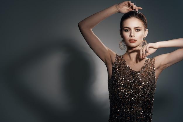 Vrolijke mooie vrouw op een gouden jurk lichte make-up studio luxe