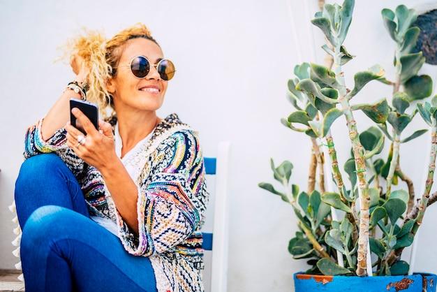 Vrolijke mooie vrouw portret gebruik mobiele telefoon buiten met plant en blauwe stoelen buiten thuis