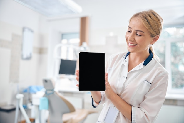 Vrolijke mooie vrouw staat in een moderne tandartspraktijk en toont digitale toushpad in handen