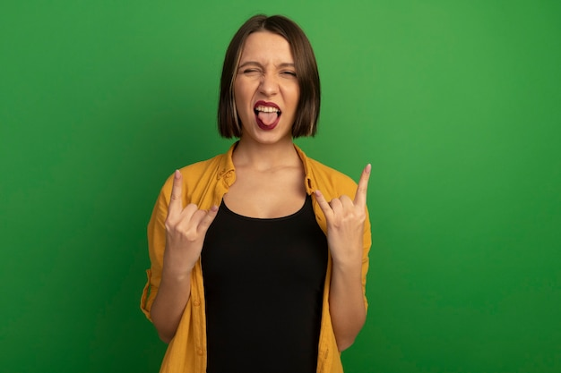 Vrolijke mooie vrouw steekt tong uit en gebaren hoorns handteken met twee handen geïsoleerd op groene muur