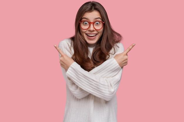 Vrolijke mooie vrouw wijst naar verschillende hoeken naar boven, heeft een vrolijke gezichtsuitdrukking, draagt een bril en een witte trui