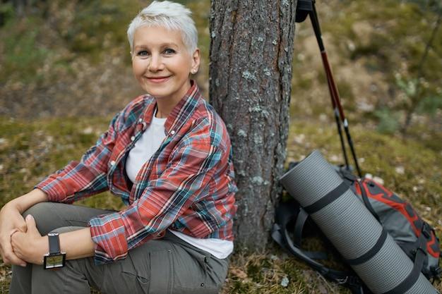 Vrolijke mooie vrouwelijke gepensioneerde m / v zittend onder de boom met rugzak en slaapmat, ontspannen tijdens haar reis in de wilde natuur. aantrekkelijke volwassen vrouw rust tijdens het wandelen in het bos