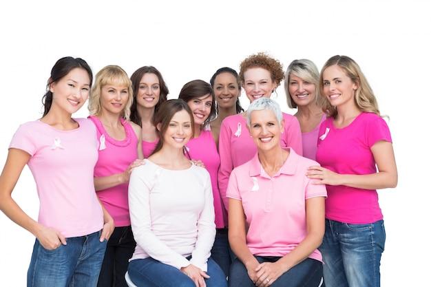Vrolijke mooie vrouwen die en roze voor borstkanker stellen dragen