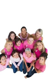 Vrolijke mooie vrouwen die omhoog dragend roze voor borstkanker kijken