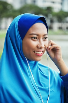 Vrolijke moslimvrouw in oortelefoons