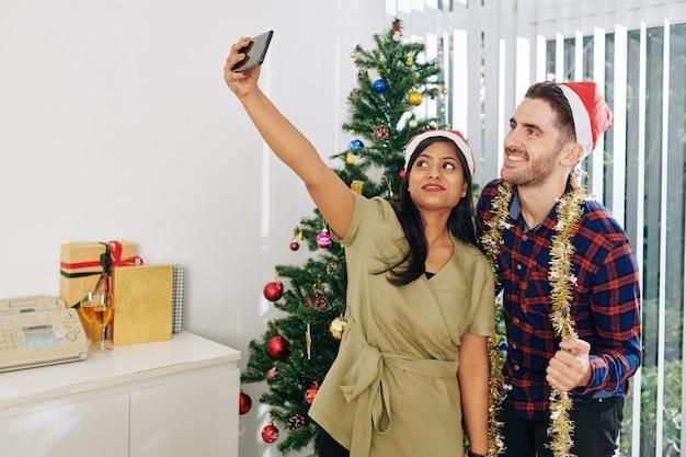 Vrolijke multi-etnische collega's in santa claus-hoeden selfie te nemen bij de kerstboom op kantoor