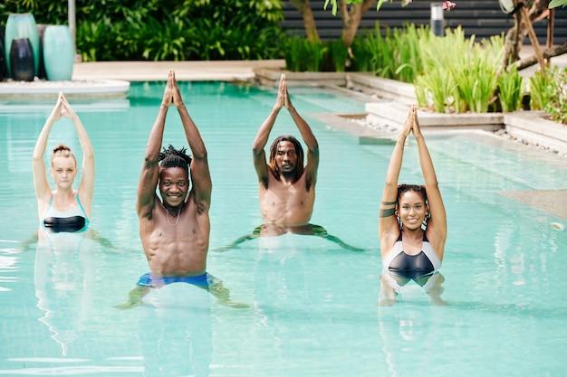Vrolijke multi-etnische fitte jonge mensen die armen in de lucht heffen tijdens het doen van oefeningen in het zwembad