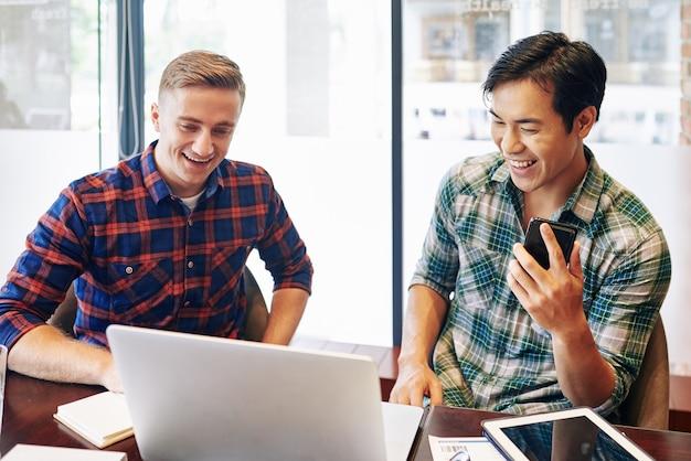 Vrolijke multi-etnische jongeren kijken naar grappige video op laptop tijdens pauze op kantoor
