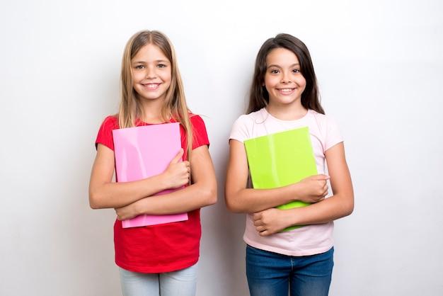 Vrolijke multi-etnische schoolmeisjes met werkboeken