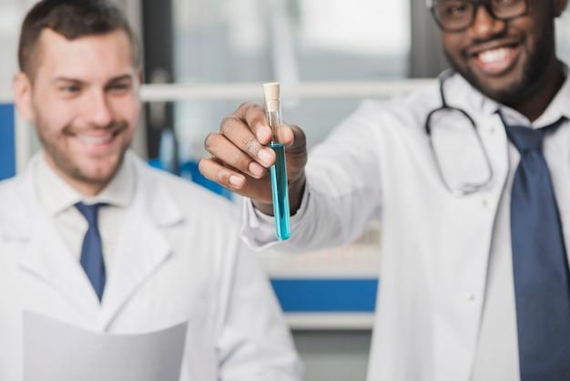 Vrolijke multiraciale artsen met reageerbuis