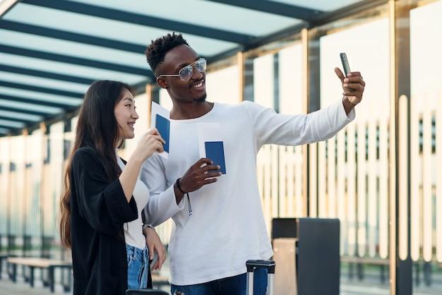 Vrolijke multiraciale mannelijke en vrouwelijke vrienden selfie maken op smartphone met paspoorten en tickets voor reis.