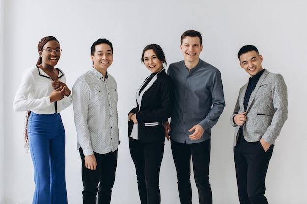 Vrolijke multiraciale professionele mensen uit het bedrijfsleven lachen samen staan in de rij in de buurt van muur, gelukkig diverse jonge werknemers studenten groep, corporate team van personeel plezier, human resource concept