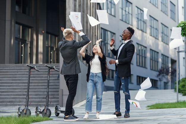 Vrolijke multiraciale vrienden die samen plezier hebben in de buurt van kantoor en zakelijke papieren documenten verspreiden