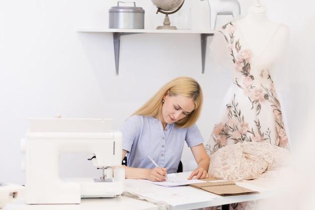 Vrolijke naaisterzitting dichtbij het naaien van hulpmiddelen