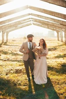 Vrolijke net getrouwd paar bruidegom en man lopen samen buiten tijdens zonsondergang