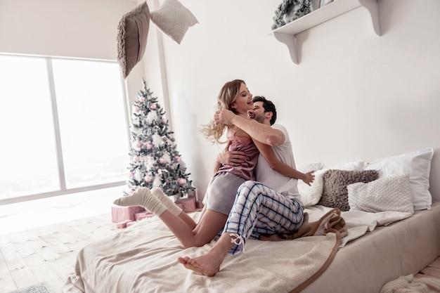 Vrolijke ochtend. brunette jonge man knuffelen zijn mooie langharige vrouw met een satijnen top